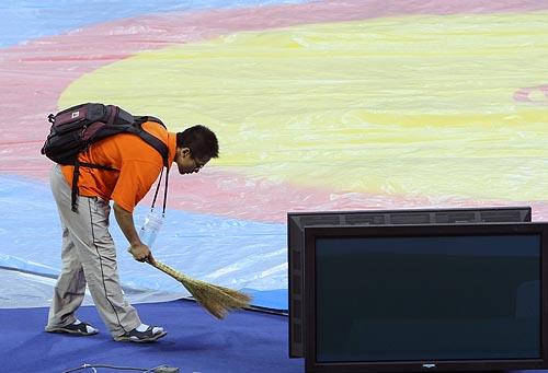 图文:农大体育馆完工 志愿者在认真打扫摔跤台