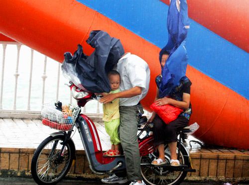 8月18日,福州街上的行人在强风下举步为艰。