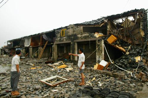 8月19日,浙江苍南,人们站在被台风摧毁的房子前面。