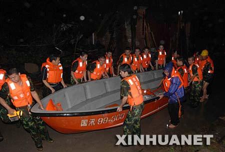 8月20日凌晨,救援人员在雨中搬运冲锋艇准备救人。