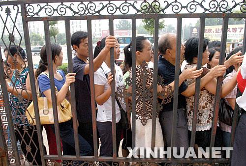 8月21日,众多家长在幼儿园外等候为孩子办理报名手续。