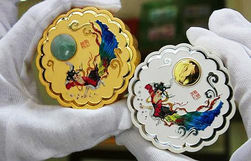 2007年8月21日,一位工作人员展示《奥运花形金玉、金银纪念章》。