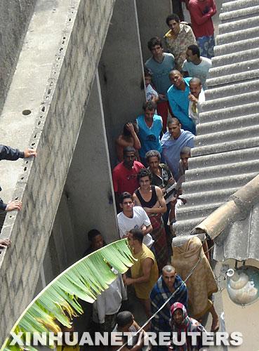 8月23日,巴西东南部米纳斯吉拉斯州蓬蒂诺瓦市一所监狱发生火灾后,囚犯们被暂时安置在监狱的院子中。