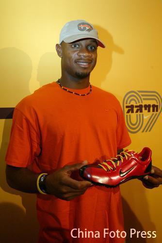 图文:牙买加名将鲍威尔接受采访 手拿红鞋拍照