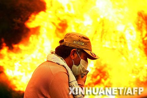 8月27日,一名村民从希腊伯罗奔尼撒半岛一个村庄附近的火场前经过。
