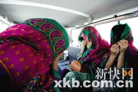 第一批获释的3名女人质裹着头巾,她们不愿意面对镜头。