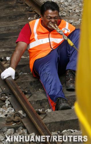 """8月30日,马来西亚""""牙齿王""""拉瑟克里什南在首都吉隆坡用牙齿拖动一列火车。"""