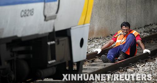 """8月30日,马来西亚""""牙齿王""""拉瑟克里什南在首都吉隆坡用牙齿拖动一列火车。新华社发"""