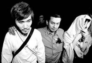 上图为8月30日,两名获释人质在工作人员护送下转移。新华社发