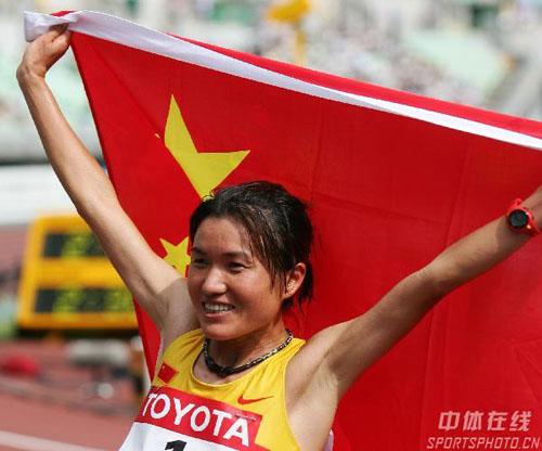 图文:女子马拉松周春秀摘银 向观众展示国旗