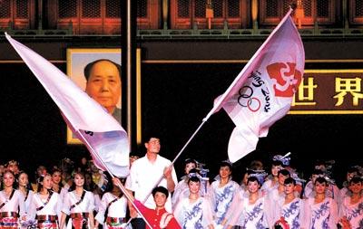 8月8日晚,庆祝倒计时一周年,小巨人挥舞着奥林匹克会旗,他的后面是另一个巨人,毛泽东的画像CFP/图