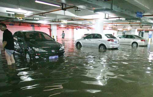 团结南路与科技路十字被大水淹没,导致隔壁小区内排水不畅,小区内的地下停车场积水严重     本报记者 王鹏 摄