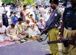 穆斯林居民在拉合尔举行礼拜,民兵荷枪实弹严密监视。