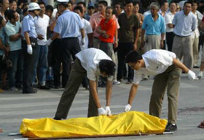 事故发生后,殡仪馆工作人员将死者尸体抬走。