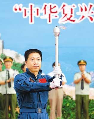 """航天英雄杨利伟举起""""中华复兴之火""""。"""