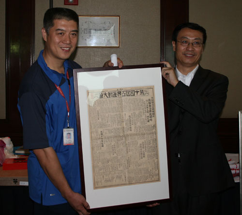 徐济成和拍卖师一起展示民国时期介绍奥运的老报纸
