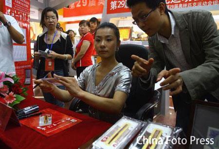 """图文:刘璇签售""""奥运火炬纪念银条"""" 仔细聆听"""
