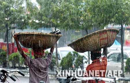 9月19日,在孟加拉国首都达卡,当地工人头顶货物在大雨中行走。新华社/法新