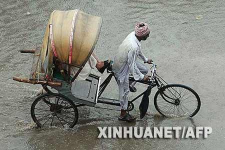 9月19日,一名三轮车夫在在印度的阿姆利则一条积水的道路上骑行。新华社/法新