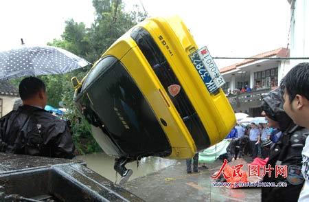 翻入河道内的跑车被吊起。 人民图片网