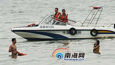女子浸泡在海水中和营救人员僵持