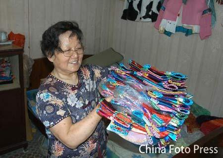 """图文:71岁裁缝做福娃""""旗袍"""" 56套代表56民族"""