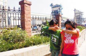 9月21日,巴南区南泉镇初级中学旁,一家水泥厂散发出难闻的气味,学生捂着鼻子通过。见习记者 李晓楠 摄