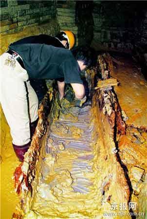考古人员正在清理挖掘出的东汉棺木。