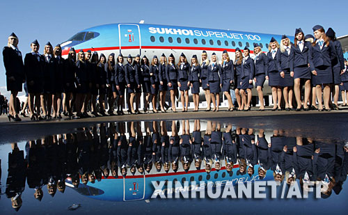 9月26日,在俄罗斯共青城的一处机场内,空乘人员列队站在一架由苏霍伊公司生产的民航客机前。