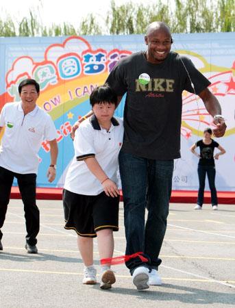 """鲍威尔(右)与特奥运动员赵曾曾做""""两人三足""""绑腿跑游戏.新华社发"""