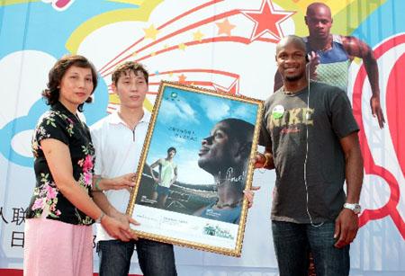 鲍威尔(右)向特奥全球信使徐闯和徐妈妈赠送带有他签名的海报。新华社发