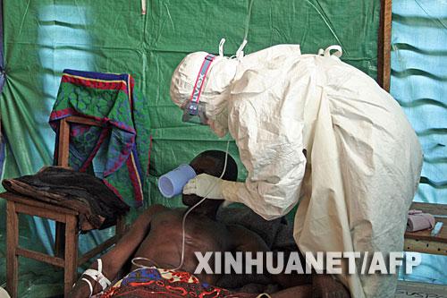 9月26日,在刚果(金)西开赛省一家医院的隔离病房,医务人员照顾一名埃博拉出血热的疑似患者。