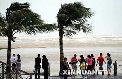 游客顶着强风在琼海市博鳌海滨游览。 新华社发
