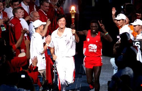 刘翔与乌干达特奥运动员手持特奥火炬跑入会