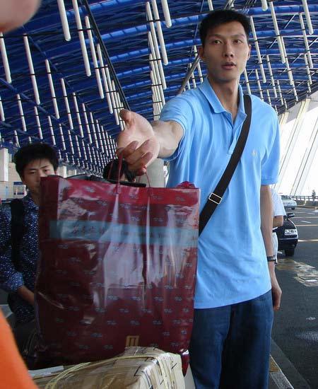 图文:易建联登机赴美 阿联手拿行李