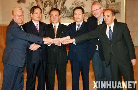 9月30日,参加六方会谈的六国代表团团长在媒体见面会上一起握手。当日, 第六轮六方会谈第二阶段会议在北京宣布休会两天。新华社记者 李明放摄
