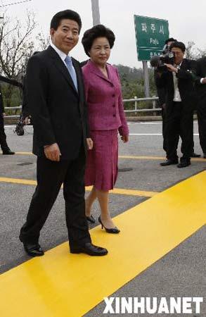 10月2日,在韩国首都首尔以北约52公里的坡州,韩国总统卢武铉(左一)与夫人权良淑(左二)跨越军事分界线。当日,韩国总统卢武铉跨过了韩朝军事分界线,成为首位跨越军分线入朝的韩国总统。新华社发