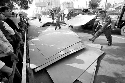 图为上午9时30分左右,附近市场的保安帮助清理路中的密度板