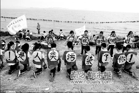 三十多名学生身穿统一的义工服装,背贴大字宣传环保。实习生王子荣本报记者 吴峻松摄