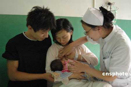 """资料图:7月31日上午,山东聊城市东昌府区妇幼保健院的护士向刚成为母亲的王女士传授母乳喂养、新生儿护理方面的知识。8月1日至7日是第十四个世界母乳喂养周,今年的主题是:""""母乳喂养和家庭食物——关爱与健康""""。东昌府区妇幼保健院采取多种形式向年轻妈妈开展母乳喂养宣传活动,广泛普及母乳喂养和婴儿出生6个月后添加食物的知识,以提高婴幼儿健康水平。 中新社发 张振祥 摄"""