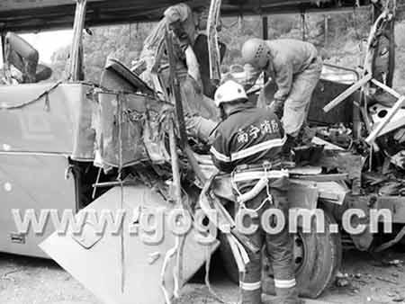 消防员在被撞得面目全非的大客车中抢救伤者