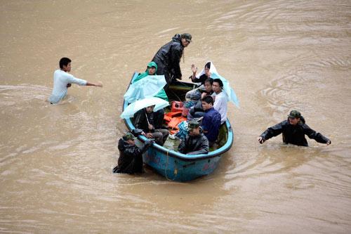 10月8日,杭州,武警战士使用冲锋舟帮助受困居民撤离被洪水淹没的街道。