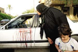 9日,在伊拉克首都巴格达市中心,一名妇女查看发生惨案的汽车。 新华社/法新
