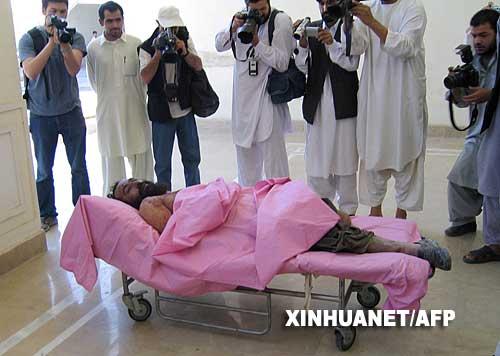 5月13日,在阿富汗坎大哈省省会坎大哈市,记者们拍摄塔利班组织高级领导人毛拉达杜拉的尸体。毛拉达杜拉是12日在阿南部赫尔曼德省被击毙的,他的尸体已从赫尔曼德省运到坎大哈省省会坎大哈市。新华社/法新