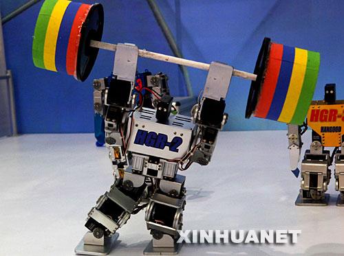 10月15日,娱乐机器人在高交会上表演举重。一批具有自主知识产权的娱乐类机器人在深圳举行的第九届高交会上亮相,它们表演聊天、唱歌、跳舞等节目,吸引人们关注。新华社记者周文杰摄