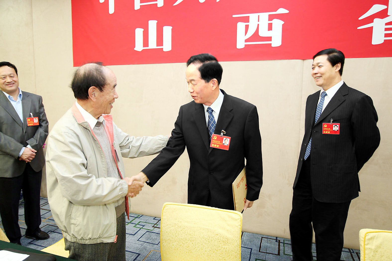 图为贾春旺与山西代表团李立功(左一)代表亲切交谈.