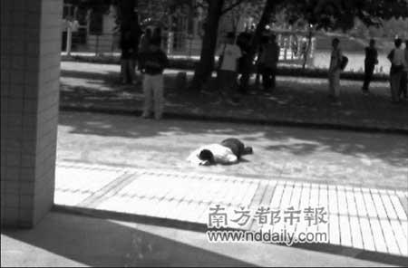 广东工业大学龙洞校区一男子坠楼后,学校门口保安注视学校出入人员。小图:有人在该校BBS上贴出图片,据称图中伏地者正是跳楼坠亡的男子。云南信息报记者杨映波摄