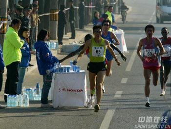 图文:07北京马拉松开跑 运动员跑过供水点