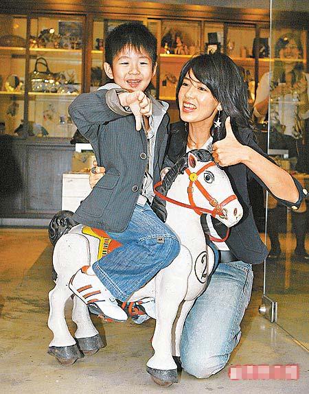 林美贞(右)新店昨开幕,儿子骑上店里摆设的古董马为妈妈打气。