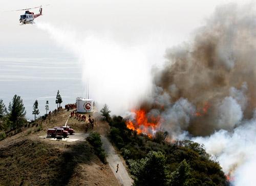 10月22日,在加州马利布,一架消防直升机在灭火,由圣安娜焚风引起的火灾,目前至少造成1人死亡。